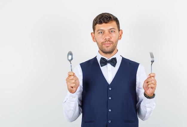 Kelner w koszuli, kamizelce, trzymający metalowy widelec i łyżkę, wyglądający na pewnego siebie.