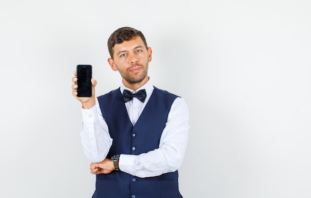 Kelner w koszuli, kamizelce, trzymający telefon komórkowy i pewny siebie, widok z przodu.