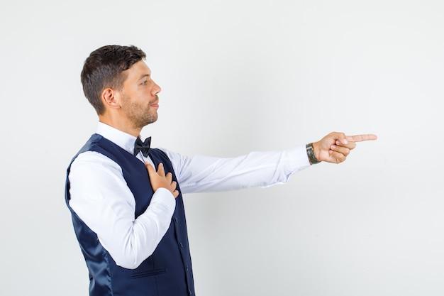 Kelner w koszuli, kamizelka skierowana w bok z ręką na piersi.