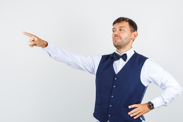 Kelner w koszuli, kamizelka wskazująca palcem w bok z ręką w talii i wyglądająca na pewną siebie, widok z przodu.