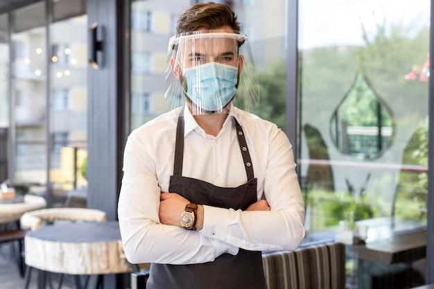 Kelner w masce i ochraniaczu