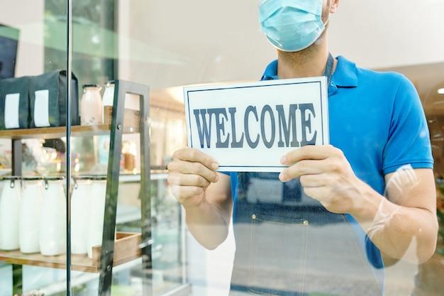 Kelner w masce medycznej przykleja powitalną naklejkę na szklanej ścianie kawiarni
