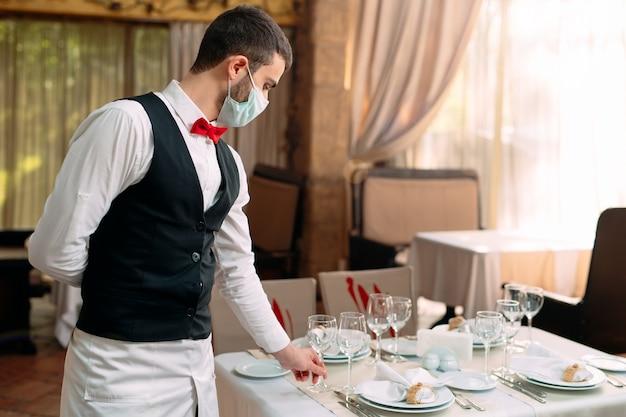Kelner w medycznej masce ochronnej podaje stolik w restauracji