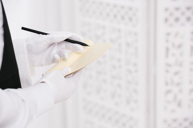 Kelner w rękawiczkach pisania zamówienia na notatnik