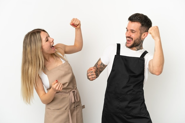 Kelner w restauracji na białym tle świętuje zwycięstwo w pozycji zwycięzcy
