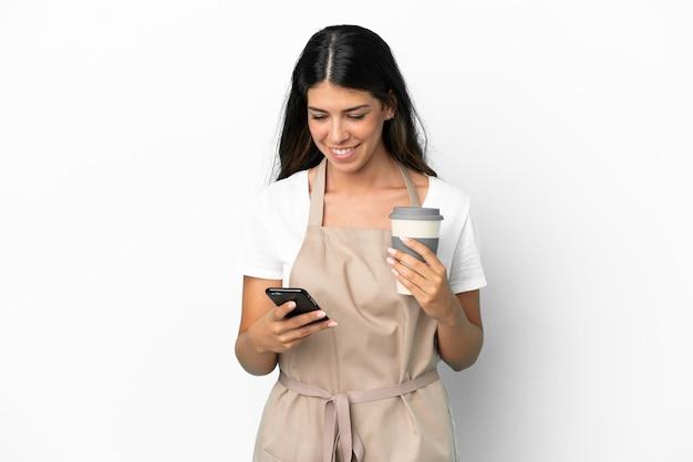 Kelner w restauracji na białym tle trzyma kawę na wynos i telefon komórkowy