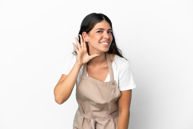 Kelner w restauracji na odosobnionym białym tle słucha czegoś, kładąc rękę na uchu