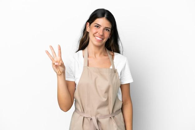 Kelner w restauracji na odosobnionym białym tle szczęśliwy i liczący trzy palcami