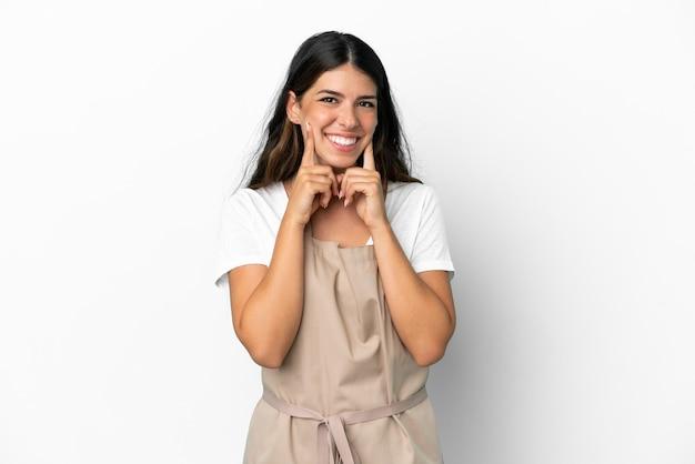 Kelner w restauracji na odosobnionym białym tle uśmiechający się z radosnym i przyjemnym wyrazem twarzy