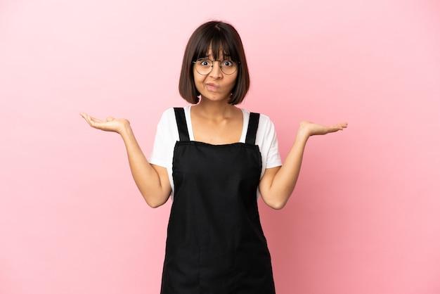 Kelner w restauracji na odosobnionym różowym tle ma wątpliwości podczas podnoszenia rąk