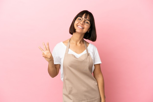 Kelner w restauracji na odosobnionym różowym tle szczęśliwy i liczący trzy palcami