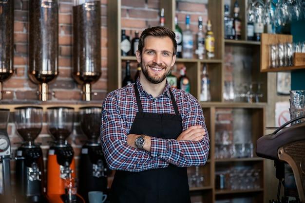 Kelner w restauracji. przystojny kelner ma na sobie kraciastą koszulkę i fartuch. ma skrzyżowane ramiona i patrzy prosto w obiektyw z uśmiechem. podawanie gorącego i zimnego napoju