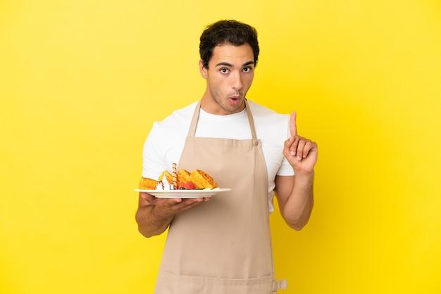 Kelner w restauracji trzymający gofry na izolowanym żółtym tle, który zamierza zrealizować rozwiązanie, podnosząc palec w górę