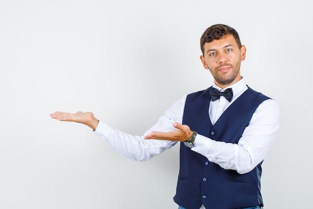 Kelner wita lub pokazuje coś w koszuli, kamizelce i wygląda wesoło. przedni widok.