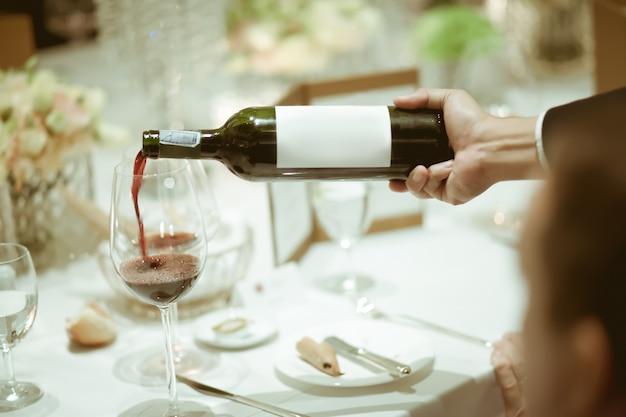 Kelner wlewając czerwone wino w kieliszek do wina na stole do serwisu w luksusowy obiad party.