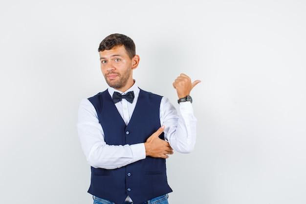 Kelner wskazujący kciuk w bok w koszuli, kamizelce, dżinsach i wyglądający na zdezorientowanego, widok z przodu.