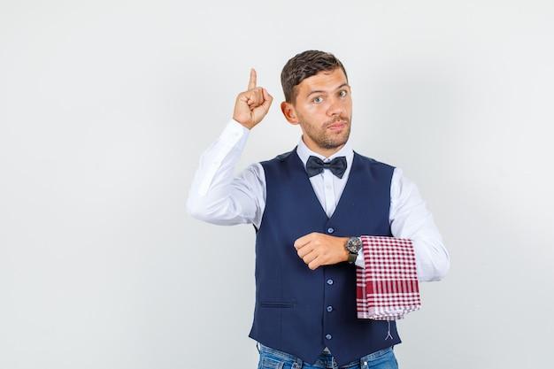 Kelner wskazujący palcem w górę w koszuli, kamizelce, dżinsach i wyglądający poważnie, widok z przodu.