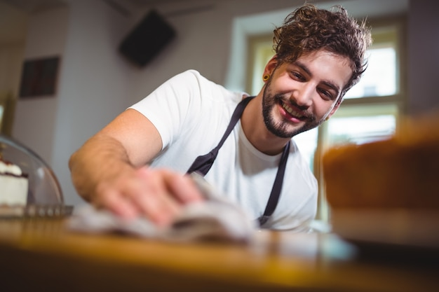 Kelner wycieranie licznik z serwetką w caf