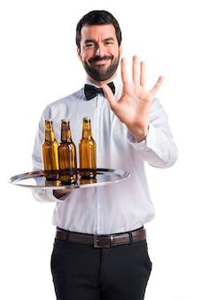 Kelner z butelkami piwa na tacy licząc pięć