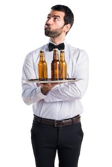 Kelner z butelkami piwa na tacy ma wątpliwości