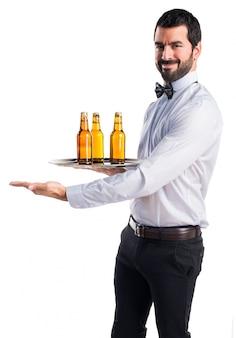 Kelner z butelkami piwa na tacy prezentuje coś