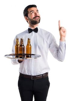 Kelner z butelkami piwa na tacy skierowanej do góry