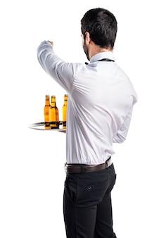 Kelner z butelkami piwa na tacy skierowanej do tyłu
