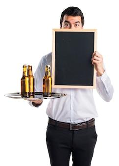 Kelner z butelkami piwa na tacy trzyma puste plakietkę