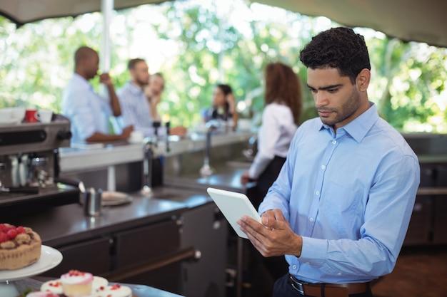 Kelner za pomocą cyfrowego tabletu w kawiarni na świeżym powietrzu