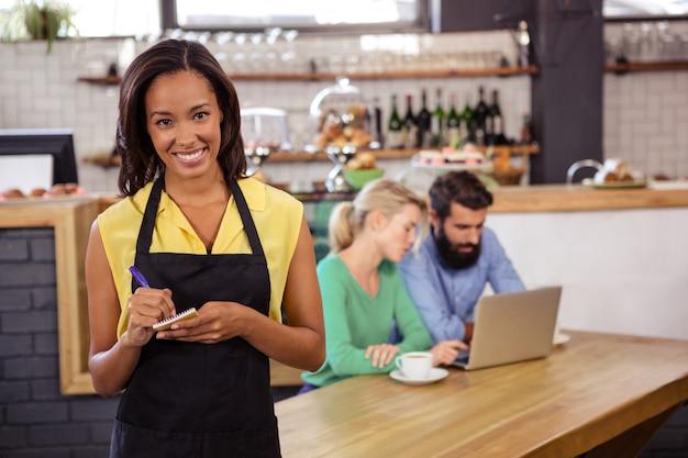Kelnerka bierze porządek na notatniku