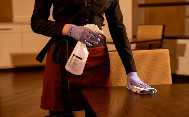 Kelnerka czyści stół ze środkiem dezynfekującym w sprayu