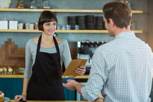 Kelnerka daje paczkę klientowi przy kasie
