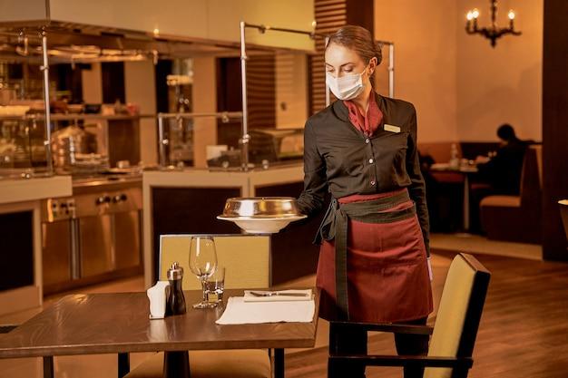 Kelnerka kładzie posiłek restauracyjny na przygotowanym stole