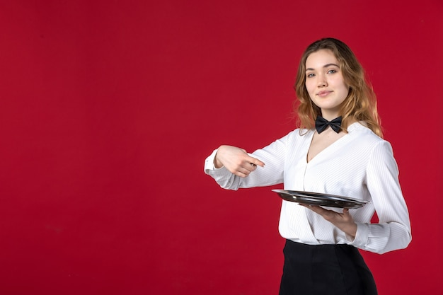 Kelnerka kobieta motyl na szyi i trzymająca tacę wskazującą na czerwonym tle