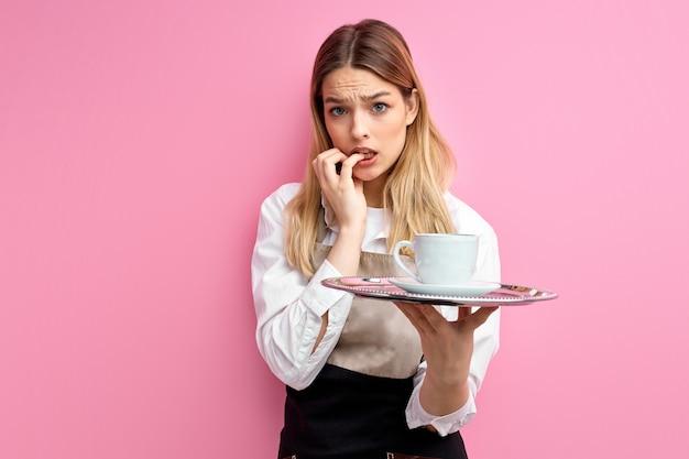 Kelnerka kobieta trzyma tacę z kubkiem na na białym tle różowym tle zestresowana i zmartwiona.