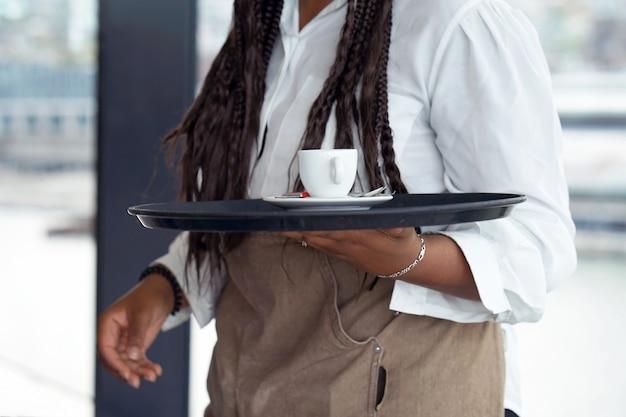 Kelnerka niesie kawę.