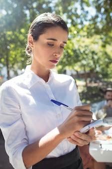 Kelnerka pisze zamówienie w notatniku