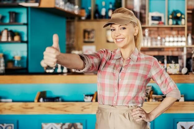Kelnerka pokazuje kciuki do góry. piękna blondynka stoi w kawiarni ubrana w kraciastą koszulę i fartuch pokazuje dłońmi znak aprobaty i wita gości w restauracji z uśmiechem