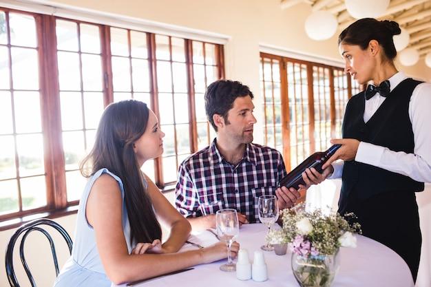 Kelnerka pokazuje wino klientowi przy stołem