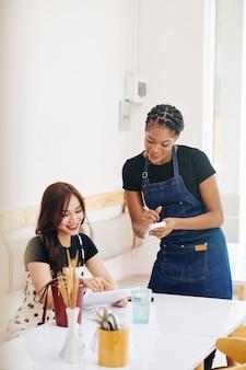 Kelnerka pomaga klientowi