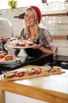 Kelnerka pozuje z ciastami