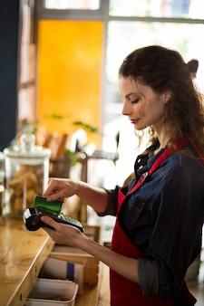Kelnerka przesuwając kartę kredytową przez czytnik kart kredytowych w kasie