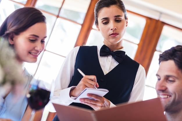 Kelnerka przyjmuje zamówienie od pary