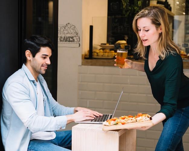 Kelnerka przynosi człowiekowi zamówienie w kawiarni