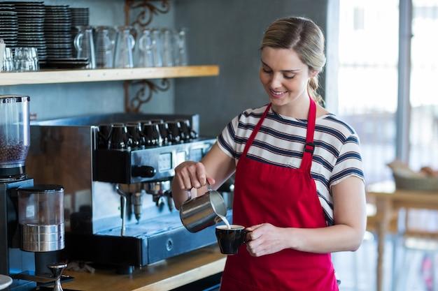 Kelnerka robi filiżance kawy przy kontuarem w kawiarni