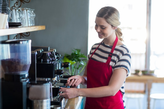 Kelnerka robi filiżance kawy w sklep z kawą