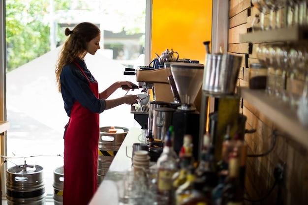Kelnerka robi filiżankę kawy przy kontuarze