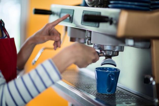 Kelnerka robi filiżankę kawy w kawie