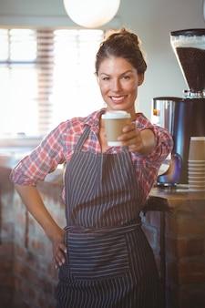 Kelnerka trzyma filiżankę kawy