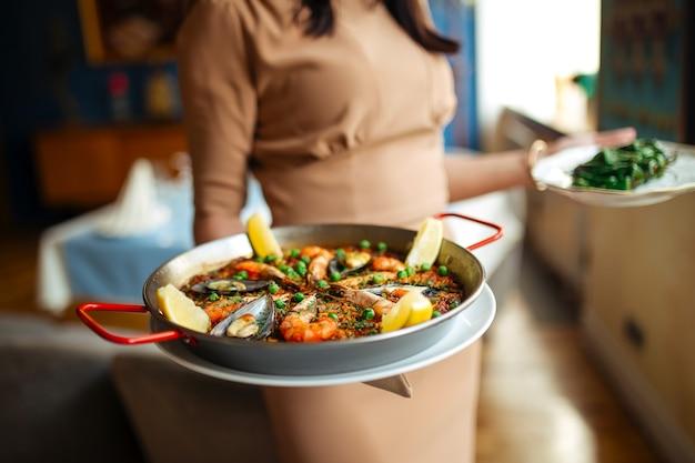 Kelnerka trzyma hiszpańskie krajowe danie z ryżu paella z owocami morza